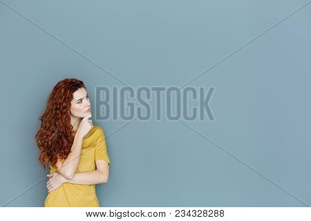 Many Thoughts. Serious Attractive Thoughtful Woman Holding Her Chin And Looking Aside While Focusing