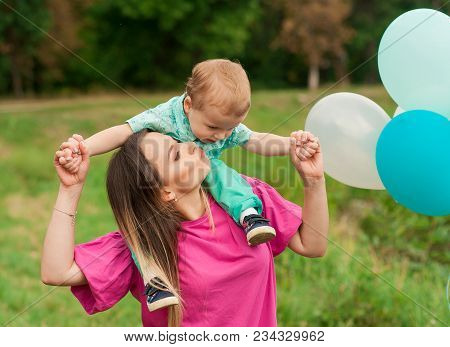 Mother And Her Little Son Spend Sunny Day In The Park. Attractive Mother Holds Cute Boy, Outdoors, C