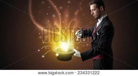 Magician hand conjure with wand  light from a black cylinder