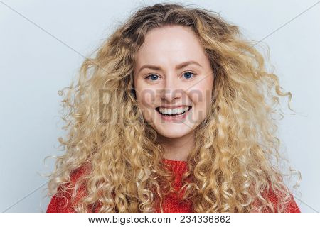 Close Up Shot Of Glad Adorable Woman With Curly Hair, Healthy Skin, Broad Smile And White Perfect Te