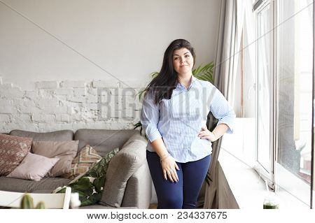 Indoor Portrait Of Overweight Plus Size Young Female With Loose Black Hair And Charming Smile Standi