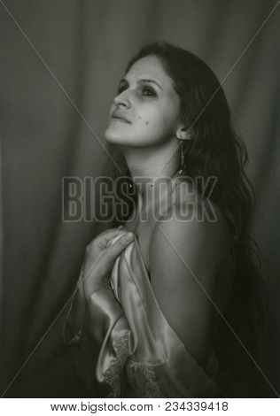 Portrait Of A Beautiful Young Woman With A Naked Shoulder. Attention! The Image Contains Granularity