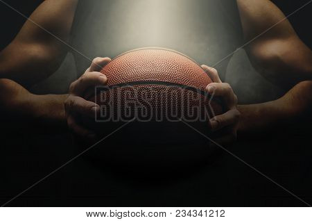 Male Basketball Player With A Ball Over Dark Background. Low Light. Fit Young Man In Sportswear Hold