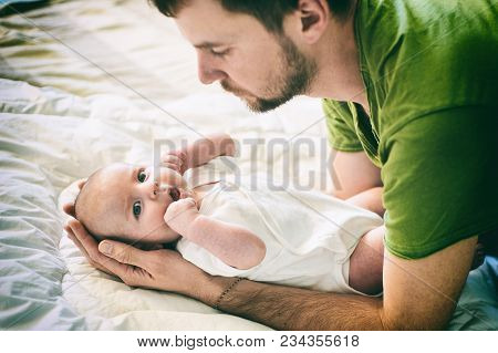 Father And Child On A White Bed. Father And Baby Boy In Diaper Playing In Sunny Bedroom. Father Make