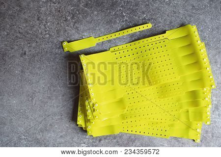 Stack Of Yellow Plastic Blank Id Wristbands Use For Entrance To Sport, Music Or Other Event To Contr