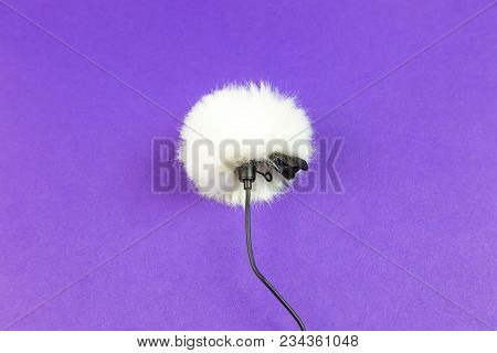 A Small Microphone For Recording High-quality Sound On A Purple Background.