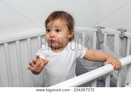 One Year Old Child In White Clothes Standing In A White Round Bed In His Nursery