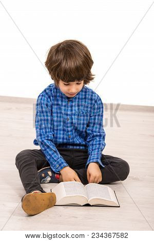 Child Boy Five Years Old Reading A Book And Sitting Down On Floor