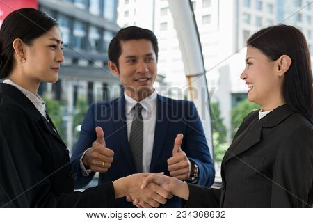 Business Man Show Thumb Up And Two Business Woman Shaking Hands And Smile For Demonstrating Their Ag