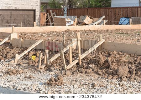 Wooden formwork concrete strip foundation for new house near completed home. Erect wooden forms fasten with drywall screws for installing concrete forms in Irving, Texas, USA. Pegging wood skeleton poster