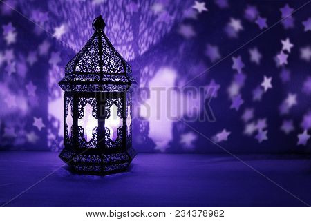 Ornamental Arabic Lantern With Burning Candle Glowing At Night And Glittering Stars Shaped Bokeh Lig