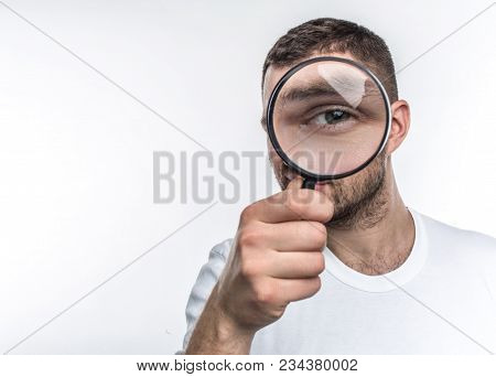 Man With Loupe Is Looking Straight Ahead And Showing His Eye Through The Glass. He Is An Investigato