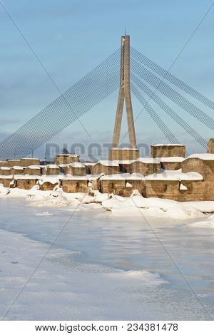 Suspension Bridge Across The River Daugava In Winter, Old Concrete Supports In The Foreground.