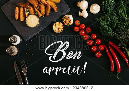 Top View Of Delicious Baked Potatoes With Sauce And Spices, Vegetables And Inscription Bon Appetit O
