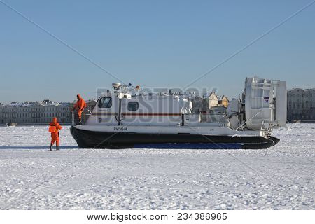 ST. PETERSBURG, RUSSIA - MARCH 4, 2018: EMERCOM staff at their hovercraft during winter swimming competitions Big Neva Cup. Winter swimmers from 12 countries take part in the competitions