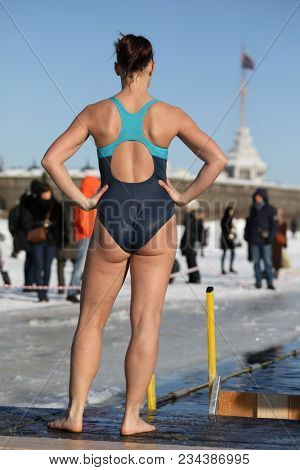 ST. PETERSBURG, RUSSIA - MARCH 4, 2018: Female amateur winter swimmer at ice hole during Big Neva Cup. Winter swimmers from 12 countries aged from 12 to 78 take part in the competitions this year