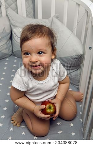 One Year Old Baby Boy Sitting In Bed With A Red Apple