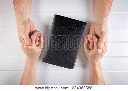 Aged Man/husband And Woman/wife Holding Hands Around A Holy Bible On White Wood Board