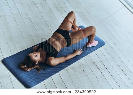 Motivated To Shape Her Body. Top View Of Young Woman In Sport Clothing Bending Over Backwards Using