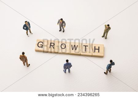 Miniature Figures Businessman : Meeting On Growth Word By Wooden Block Word On White Paper Backgroun