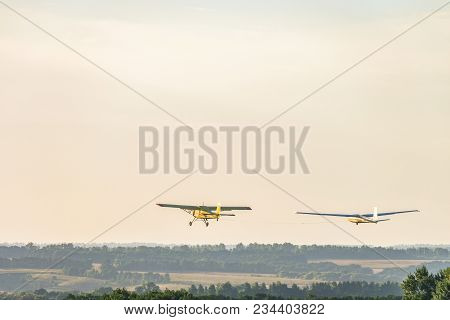 Small Light-engine Sport Plane Flying In The Evening Sky Pulls On A Rope The Glider Plane. Flight Ov