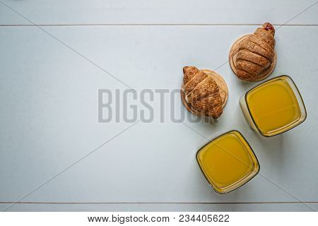 Croissants And Orange Juice In Glass. French Breakfast. Orange Juce On The Wooden Table. Top View