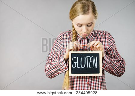 Young Woman With Braided Hair Holding Small Black Board With Gluten Sign. Bakery And Bread Allergy P