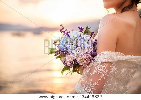 Bride Holds Wedding Bouquet From Lavender, Hydrangea And Stands On Background Of Sea And Sunset Afte