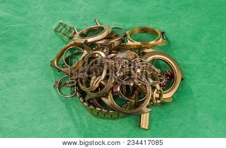 A Scrap Of Gold. Old And Broken Jewellery, Watches Of Gold And Gold-plated On A Green Background.