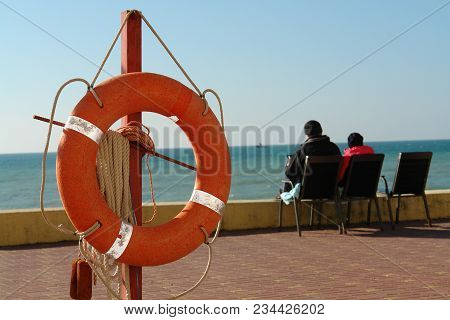 Two People Sitting On Chair Near The Sea. Lifebuoy In The Foreground.