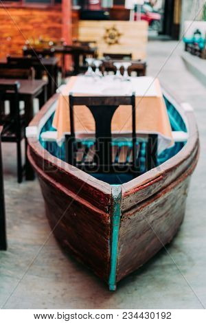 Unusual Restaurant Interior: Dining Table In The Colorful Fish Boat. Marine Ambience.