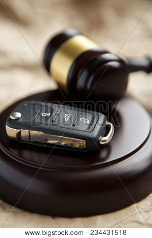 Close-up Of Gavel And Car Key On Sounding Block Against