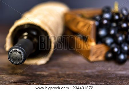 Close Up Wine Bottle And Fresh Ripe Grapes In Wooden Box. Selective Focus