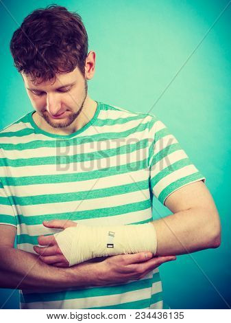 Fractures And Dislocations Concept. Man With Hand In Bandage. Helpful Medication For Painful Palm Ar