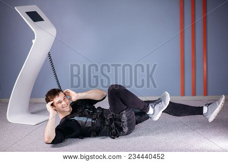 Male Athlete Wearing Ems Suit Doing Abs Exercise Or Sit Ups