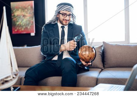 Bearded Arab Businessman In Suit Looking At Globe With Loupe On Couch At Hotel Room.