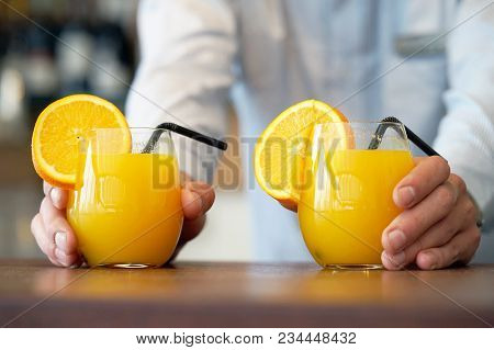 The Barman Gives Two Glasses Of Orange Juice To The Client Of The Hotel Restaurant. The Waiter Trans