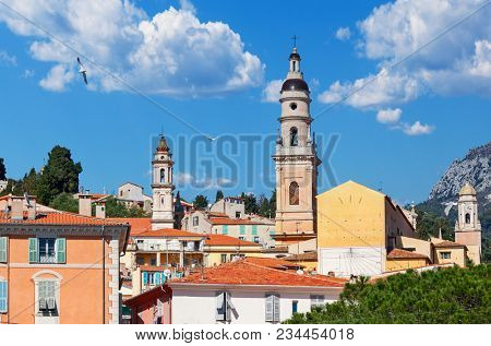 View of church belfry among colorful houses under blue sky in small town of Menton in France.