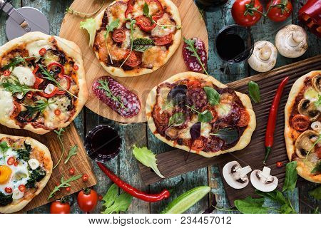 Pizza And Wine Party. Homemade Rustic Pizzas And Raw Ingredients Served With Red Wine On Oak Choppin