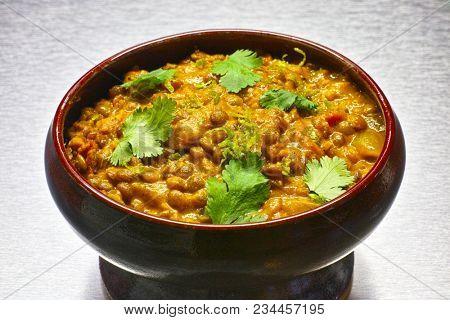 Moong Dal, indian vegetarian lentil soup, in terra cotta bowl. Aluminium background.