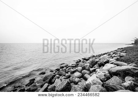 Rocks By The Seashore In A Black And White Photo In The Fall
