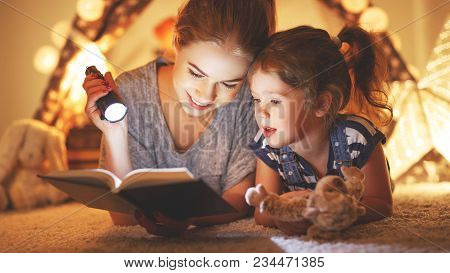 Reading And Family Games In   Tent. Mother And Child Daughter Reading Book And Flashlight Before Goi