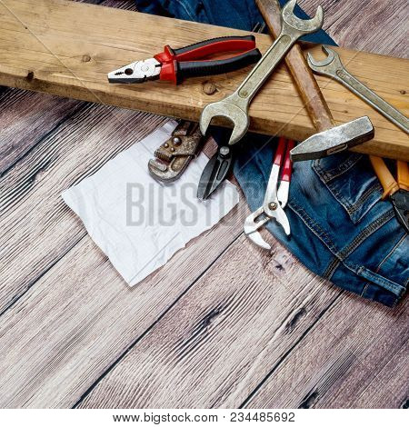 Wooden Board, Hammer, Pliers And A Set Of Spanners On A Wooden Background With Space For Text
