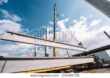 Industrial Heavy Duty Crane Lifting Precast Cement Beams And Pillars On Construction Site
