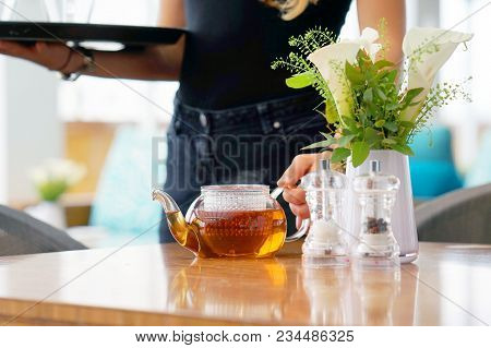 The Waitress Puts Glass Teapot With Tea And Cup On A Table At A Restaurant Client. Morning Time. A C