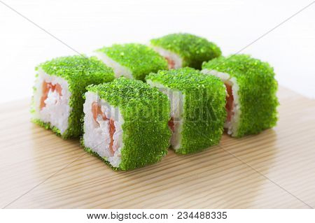 One Set Of California Rolls Covered Green Tobiko Or Masago Caviar On A Wooden Board On A White Backg