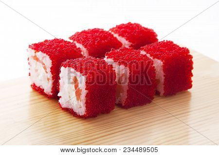 One Set Of California Rolls Covered Red Tobiko Or Masago Caviar On A Wooden Board On A White Backgro