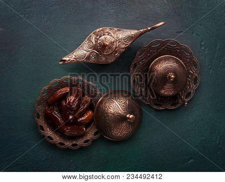 Bronze plate with dates, coffe cup and aladdin lamp  on dark green wooden background.  Ramadan kareem.  Flat lay.