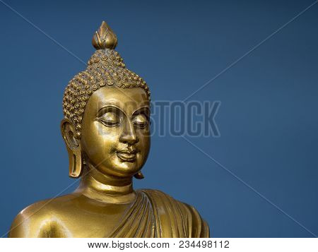 Golden Antique Buddha Statue. The Background Is Light Slate Gray. The Face Of The Buddha Turned To T