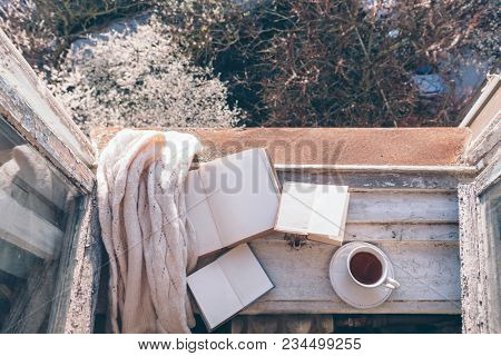 Old window with the view from inside on blooming tree in backyard. Opened book, cup of tea or coffee and knitted sweater on windowsill. Cozy spring weekend concept.